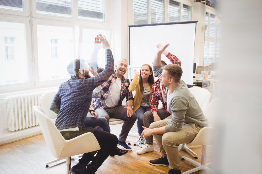 Excited creative business people giving high-five in meeting room at creative office